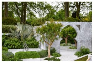 A beautiful spacious garden with an islamic geometric white marble arch to once side and many green trees including a palm
