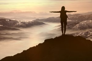 Woman silhouette sunset standing on top of a mountain =arms outstretched