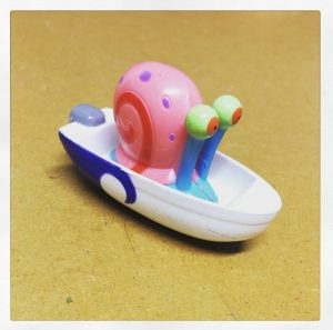 A plastic children's toy a multicoloured snail sitting in a plastic speedboat