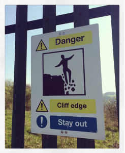 Danger poster on the railings around Riddlesdown quarry image of person slipping over the ledge