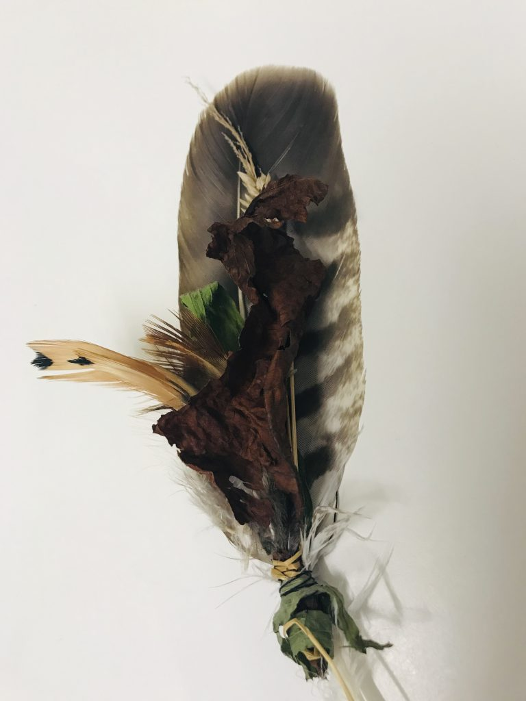A bundle of colourful jay feathers bound together with leaves and sealed with wax, to illustrate a post about gentleness